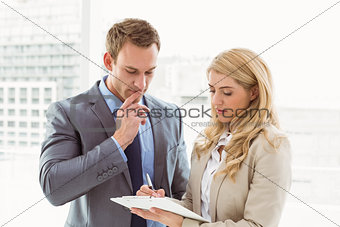 Businessman and secretary looking at diary