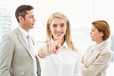 Businesswoman pointing at you with colleagues in office