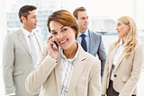 Businesswoman using mobile phone with colleagues behind