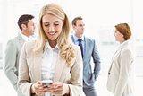 Businesswoman text messaging with colleagues in meeting behind
