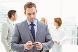 Businessman text messaging with colleagues in meeting behind