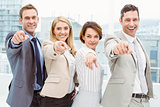 Happy business people pointing at you in office