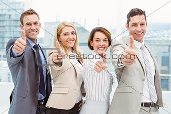 Business people gesturing thumbs up in office