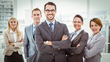 Young business people with arms crossed in office