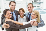 Business people with arms around in office
