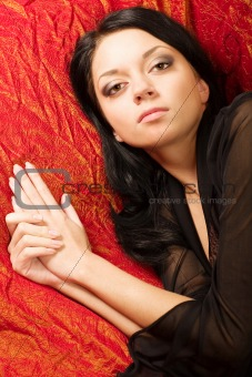 Beautiful girl lying on a bed. Portrait.