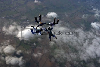Four skydivers building a formation