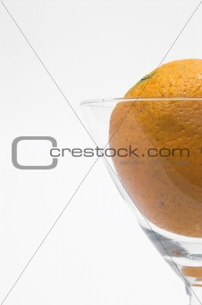 A fresh orange in a martini glass.