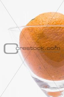 A fresh orange in a martini glass.
