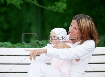 happy mother with baby on the bench