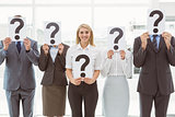 Business people holding question mark signs in office