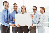 Young business people holding blank board in office