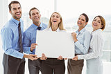 Cheerful business people holding blank board in office