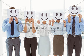 Business people holding happy smileys on faces