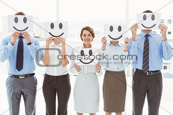 Business people holding happy smileys