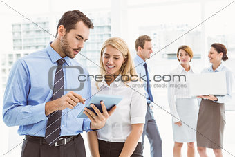 Business couple using digital tablet with colleagues behind