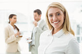 Businesswoman with colleagues behind at office