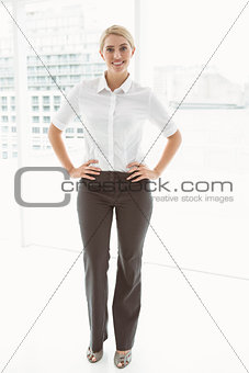 Beautiful businesswoman with hands on hips in office