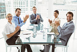 Business people clapping hands in board room meeting