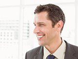 Cheerful businessman looking away at office
