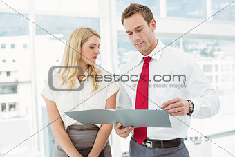 Businessman and secretary looking at file in office
