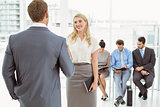 Businesspeople in front of people waiting for interview