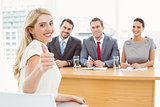 Woman gesturing thumbs up in front of corporate personnel officers