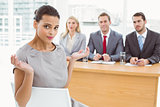 Woman sitting in front of corporate personnel officers