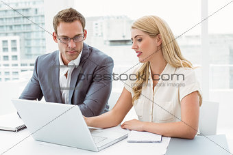 Business people using laptop at office