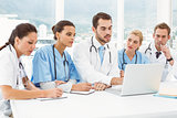 Male and female doctors using laptop
