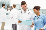 Male doctor and surgeon looking at reports