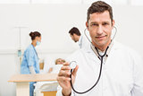 Doctor using stethoscope with colleagues and patient behind