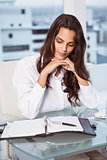 Beautiful businesswoman looking at diary in office