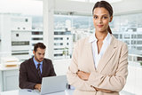 Beautiful businesswoman with arms crossed at office