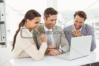Business people using laptop in office