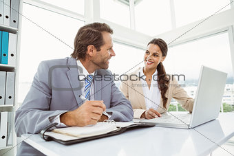 Business people with laptop and diary at office