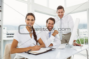 Three smiling business people at office desk