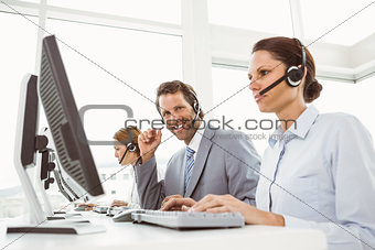 Business people with headsets using computers in office