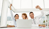 Business people cheering in front of laptop at office