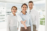Businesswoman with colleagues offering handshake at office