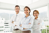 Confident business people with arms crossed in office