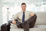 Happy businessman sitting on couch in living room