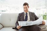 Businessman reading newspaper in living room