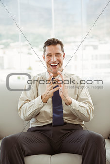 Portrait of happy businessman sitting on couch