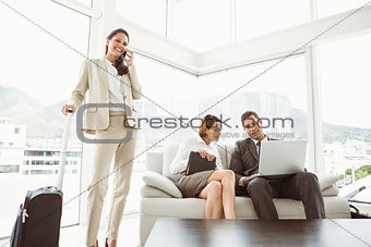 Business people using laptop and colleague with luggage