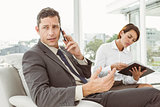 Businessman on call while secretary looks at diary