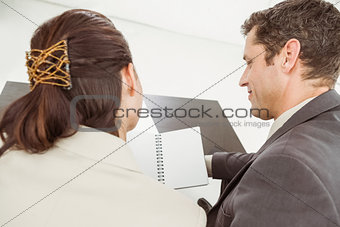 Businessman and his secretary looking at diary