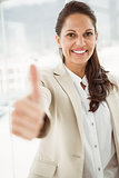 Businesswoman gesturing thumbs up in office