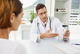 Doctor giving prescription to patient in medical office