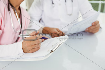Close up mid section of doctors discussing reports